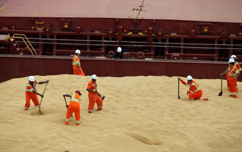 Trabalhadores carregam navio de carga com soja no Porto de Santos, Brasil